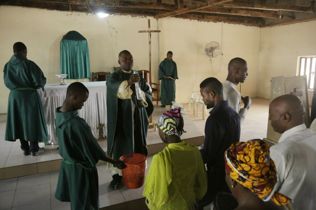 Rev. Father Maurice Kwairanga, centre, bless parishioner during a mass at St Charles Catholic Church, in Ngurore, Nigeria, Sunday, Feb. 17, 2019. Nige