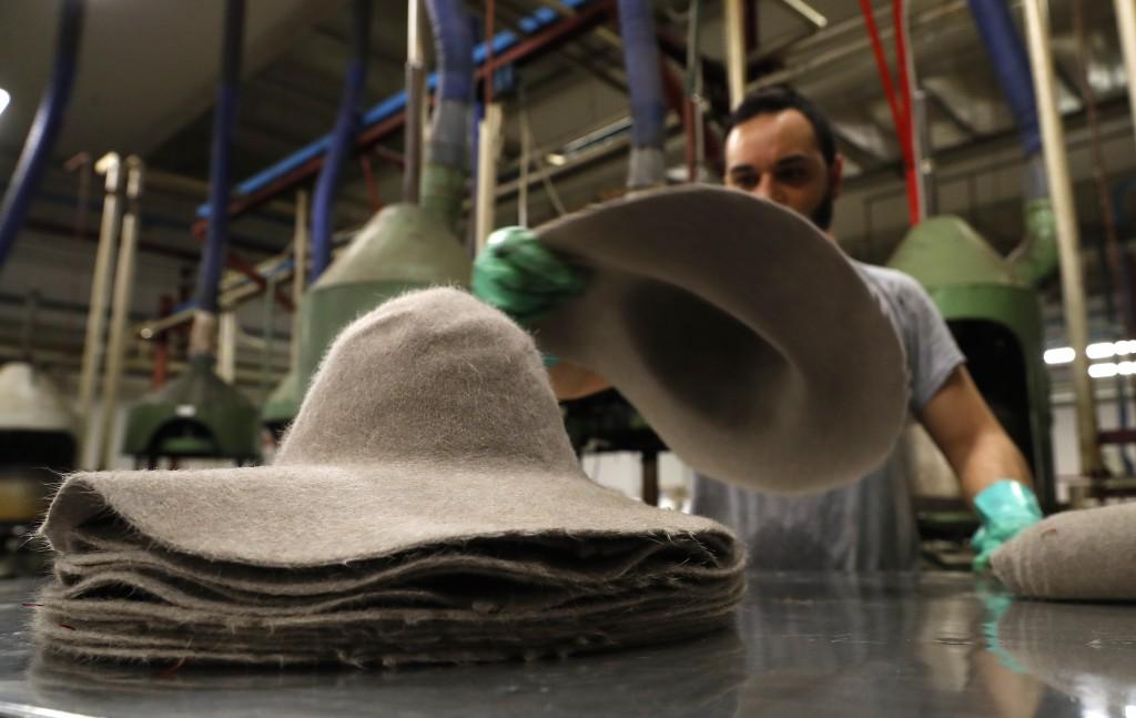 A man piles felt hats inside Borsalino's hat factory, in Spinetta Marengo, near Alessandria, Italy, Thursday, Jan. 17, 2019. Borsalino's prized felt h...