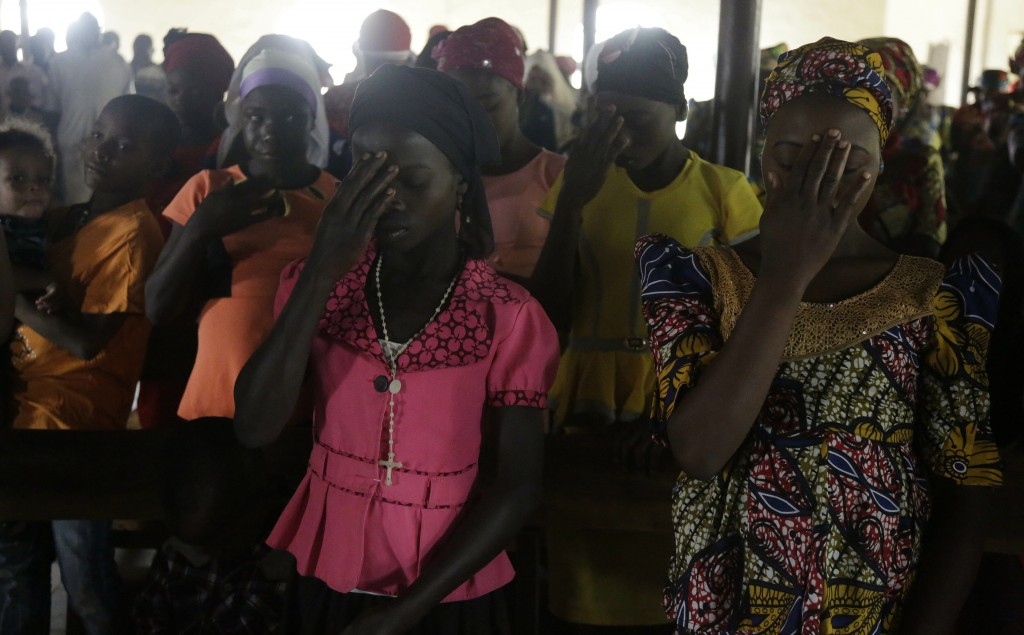 Nigerian women pray at St Charles Catholic Church, during a mass in Ngurore , Nigeria, Sunday, Feb. 17, 2019. Nigeria's top candidates on Saturday con