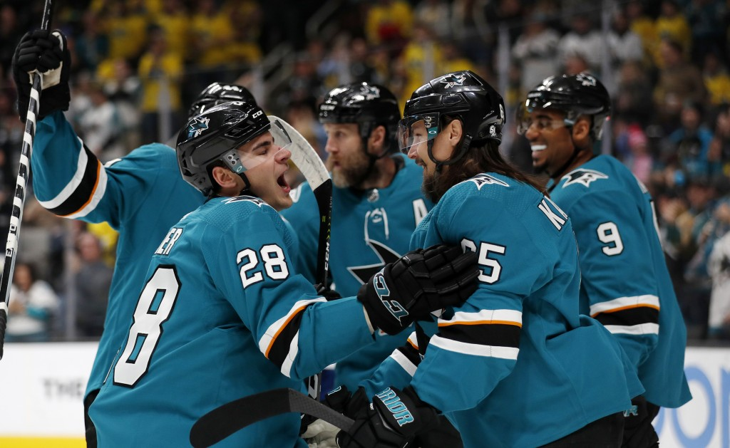 San Jose Sharks' Timo Meier (28) celebrates with Erik Karlsson (65) and Evander Kane (9) after scoring against the Vancouver Canucks during the first ...