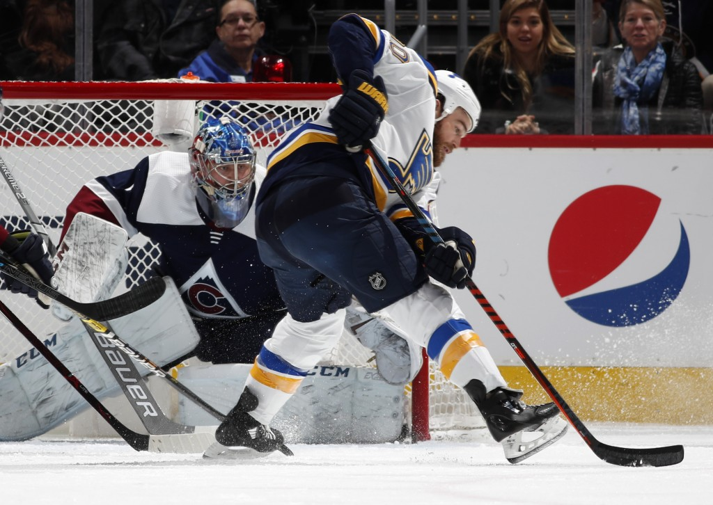 Colorado Avalanche goaltender Semyon Varlamov, back, looks to block a redirected shot off the stick of St. Louis Blues center Ryan O'Reilly in the fir...