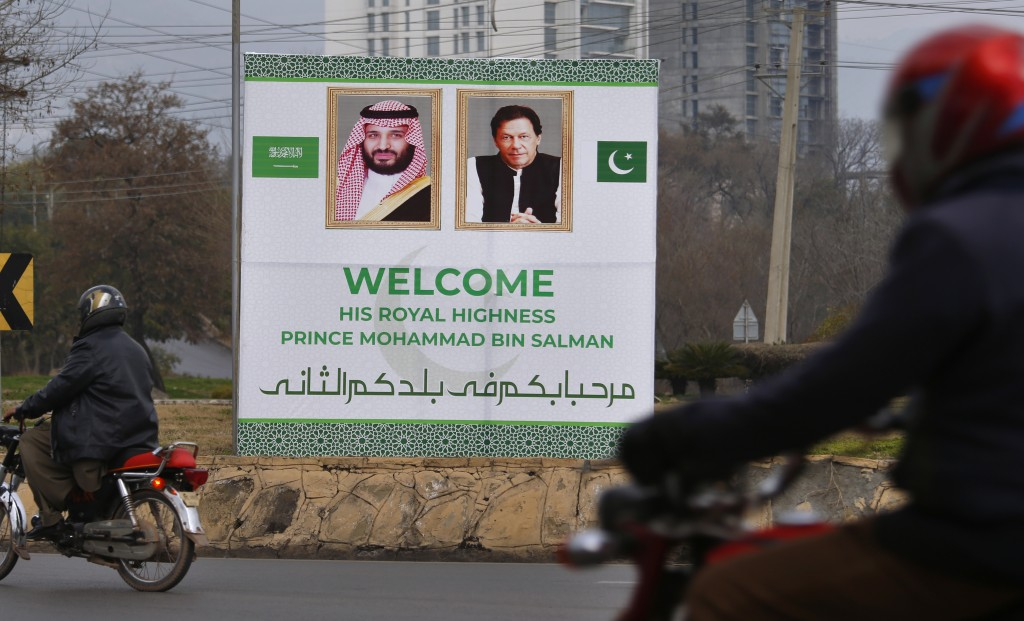 Pakistani motorcyclists pass by a billboard welcoming Saudi Arabia's Crown Prince Mohammed bin Salman displayed on the occasion of the visit by Saudi ...