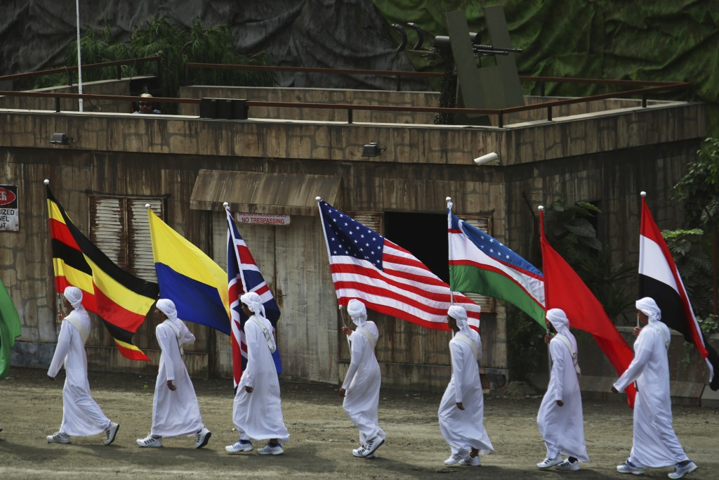 Emirati boys holding flags of the participating countries at an arms show march past a theatrical machine gun position at the opening ceremony of the ...