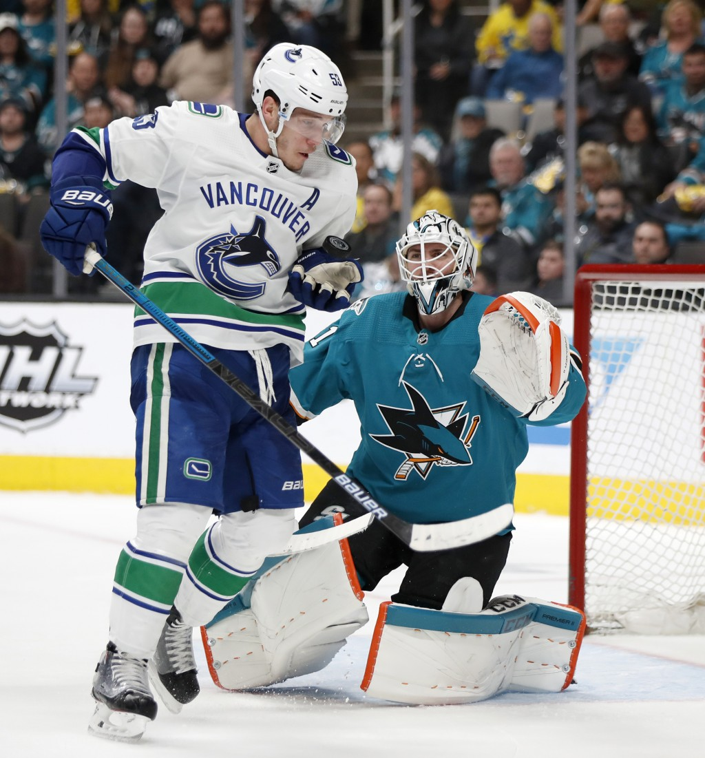 Vancouver Canucks' Bo Horvat (53) reaches for the puck in front of San Jose Sharks goaltender Martin Jones (31) during the second period of an NHL hoc...