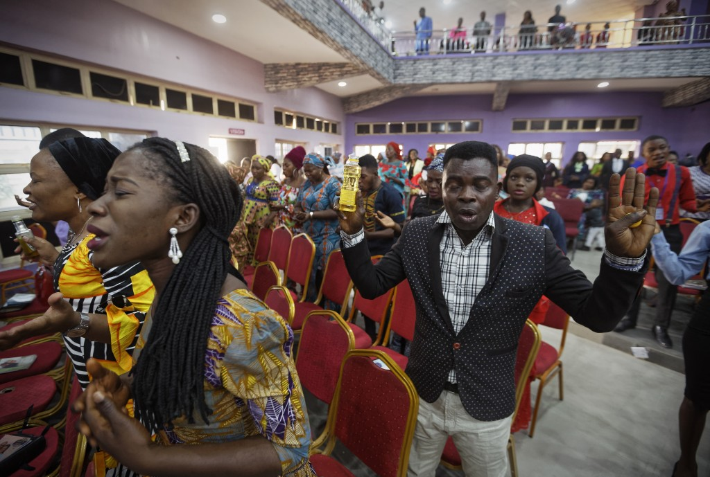 Churchgoers pray and anoint their foreheads with oil at the Living Faith church in the predominantly-Christian neighbourhood of Sabon Gari in Kano, no