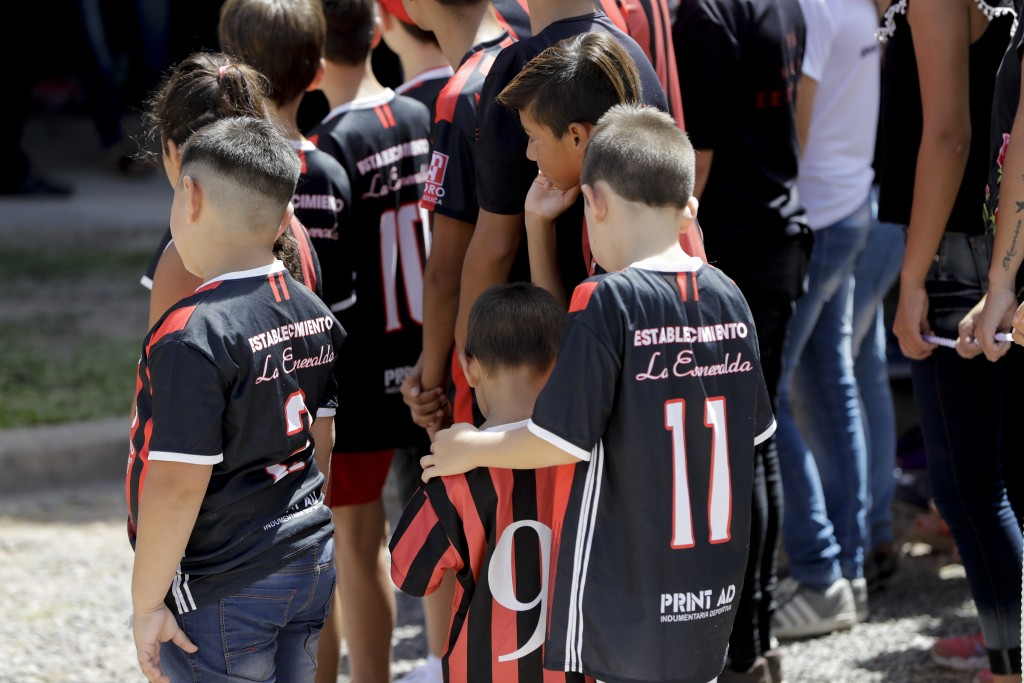Children wait for soccer player Emiliano Sala's coffin to depart for Santa Fe, after his wake in Progreso, Argentina, Saturday, Feb. 16, 2019. The Arg...
