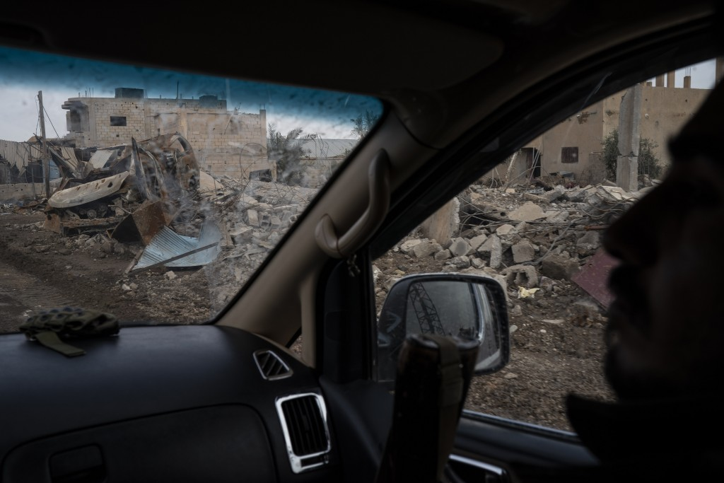 A U.S.-backed Syrian Democratic Forces (SDF) fighter rides past destroyed homes and vehicles in a village recently retaken from Islamic State militant...