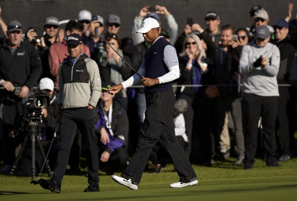 Tiger Woods reacts as the gallery cheers after making birdie on the ninth hole as second round play continues during the Genesis Open golf tournament ...