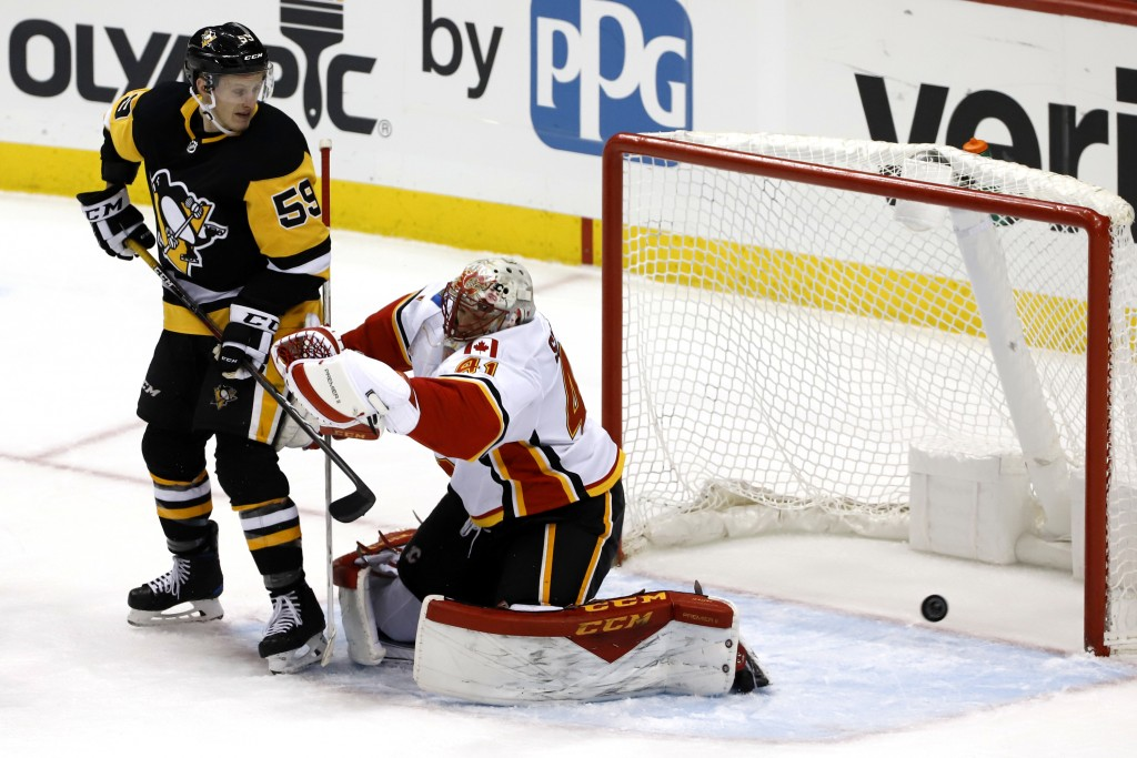 Pittsburgh Penguins' Jake Guentzel (59) defects the puck past Calgary Flames goaltender Mike Smith (41) for a goal in the first period of an NHL hocke...