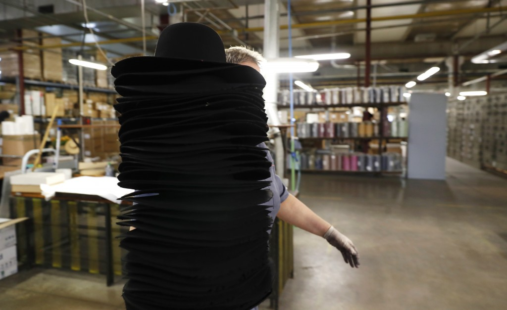 A woman holds a pile of hats inside Borsalino's hat factory, in Spinetta Marengo, near Alessandria, Italy, Thursday, Jan. 17, 2019. Borsalino's prized...