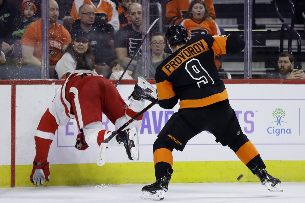 Detroit Red Wings' Justin Abdelkader, left, goes flying after trying to check Philadelphia Flyers' Ivan Provorov during the first period of an NHL hoc...