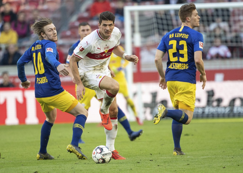 Stuttgart's Mario Gomez, center, challenges for the ball with Leipzig's Emil Forsberg, left, during the German Bundesliga soccer match between VfB Stu...
