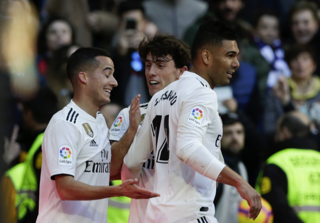 Real Madrid's Casemiro, right, celebrates with teammates Lucas Vazquez, left, and Alvaro Odriozola after scoring his team's first goal during a La Lig...