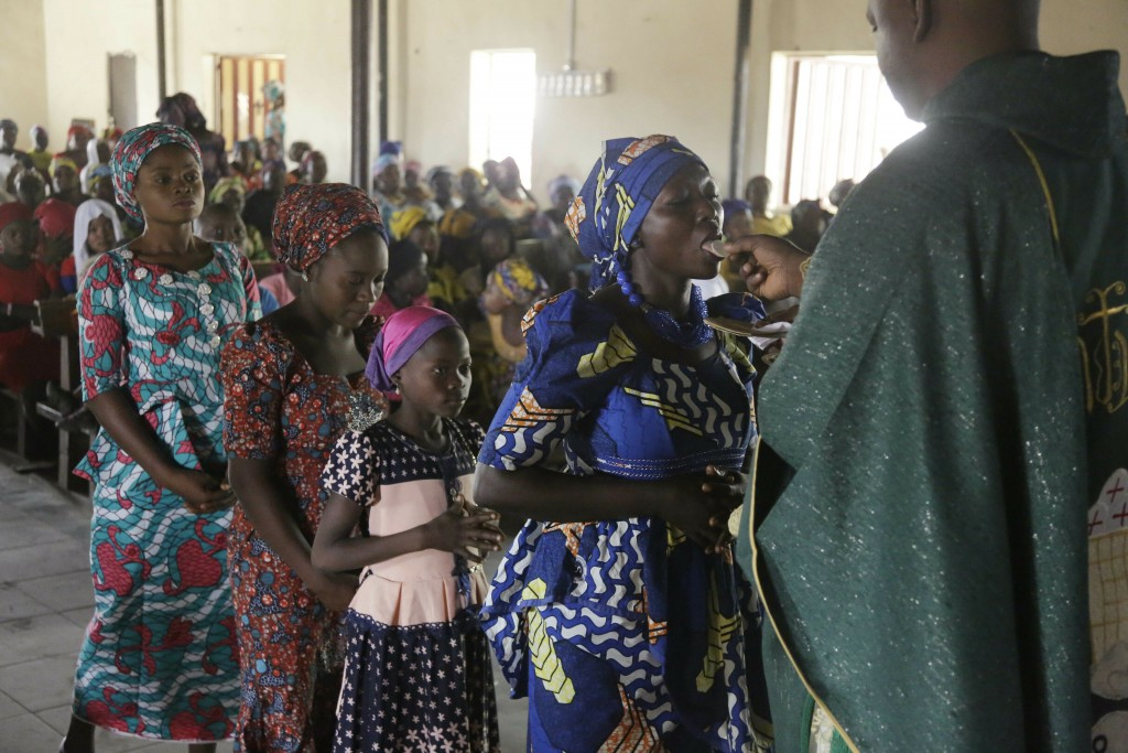 Nigerian women take communion at St Charles Catholic Church, during a mass in Ngurore , Nigeria, Sunday, Feb. 17, 2019. Nigeria's top candidates on Sa...