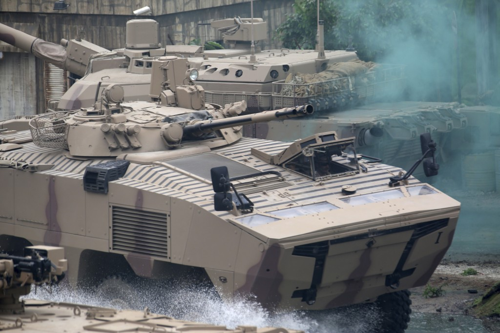 Soldiers in an armored personnel carrier roar through a military demonstration at the International Defense Exhibition and Conference in Abu Dhabi, Un...
