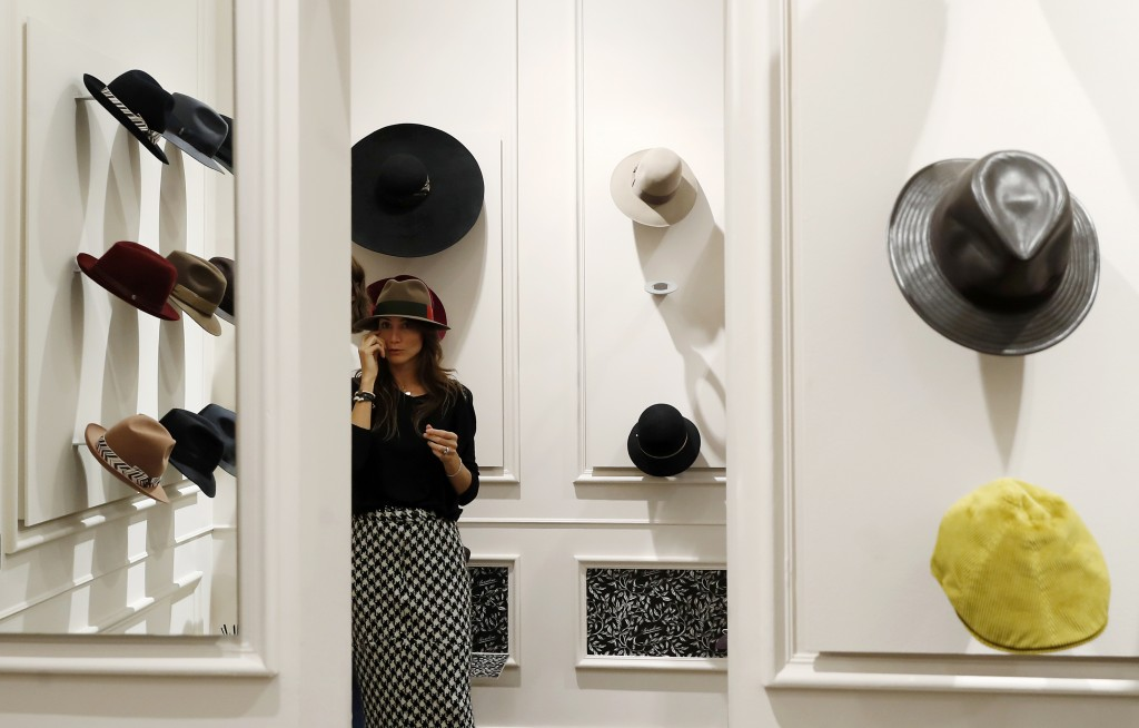 A woman tries a hat inside a Borsalino hat store in downtown Milan, Italy, Wednesday, Jan. 16, 2019. If the traditional Italian hat-maker Borsalino wa...