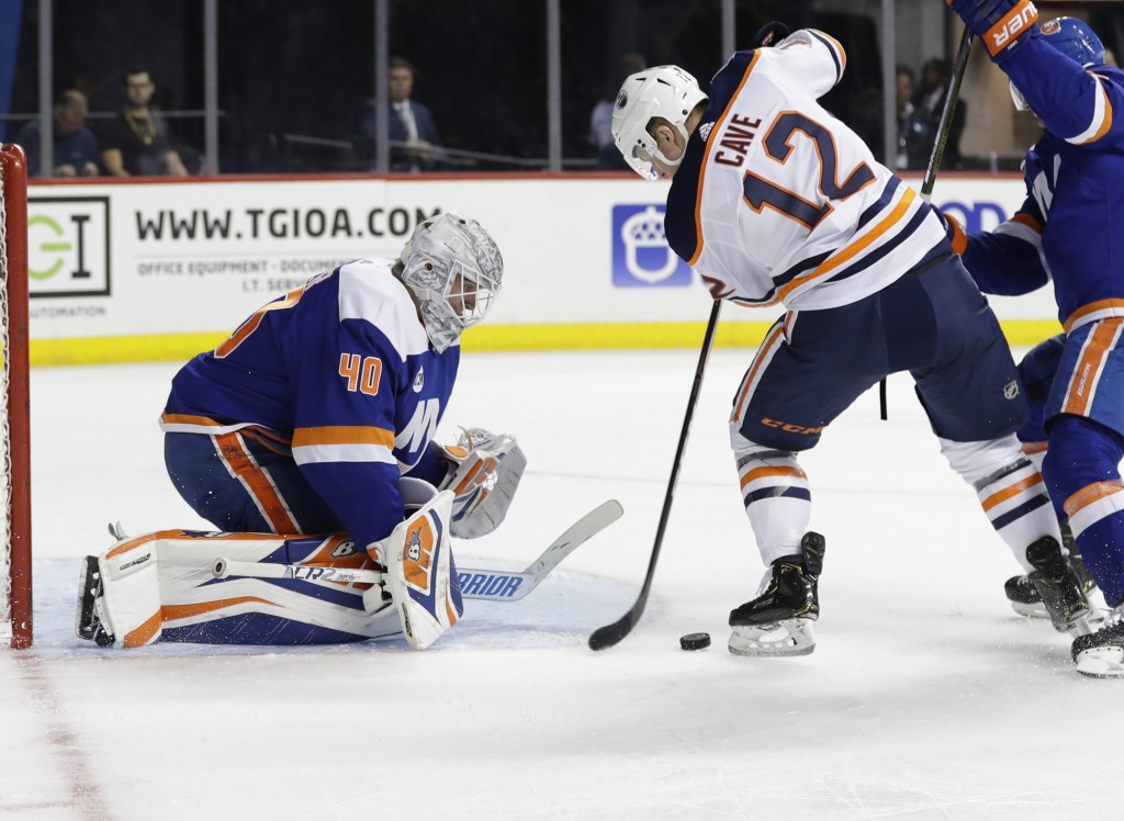 New York Islanders goaltender Robin Lehner (40) stops a shot by Edmonton Oilers' Colby Cave (12) during the first period of an NHL hockey game Saturda...