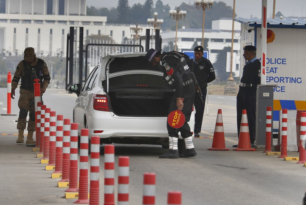 A Pakistani army soldier stands guard while police officers search a vehicle at a checkpoint near presidency to ensure security ahead of Saudi Arabia'...