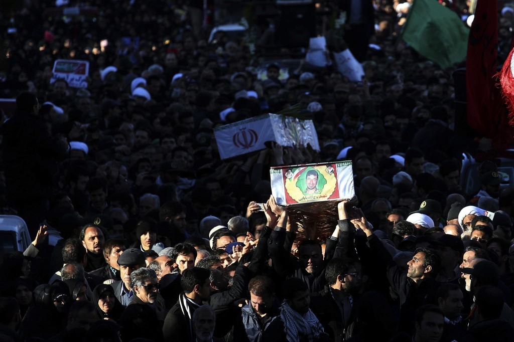 Mourners carry flag-draped caskets during a mass funeral for those killed in a suicide car bombing that targeted members of Iran's powerful Revolution...