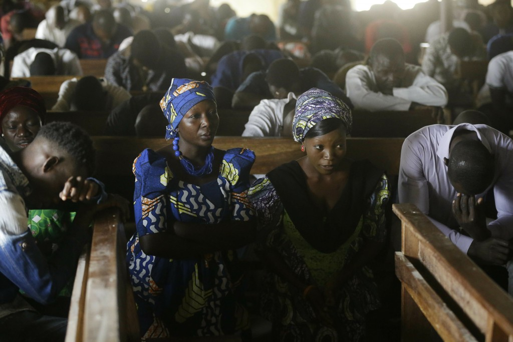 People pray at St Charles Catholic Church, during a mass in Ngurore , Nigeria, Sunday, Feb. 17, 2019. Nigeria's top candidates on Saturday condemned t...