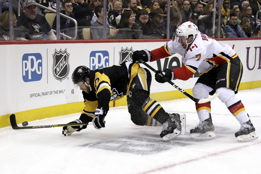 Calgary Flames' TJ Brodie (7) checks Pittsburgh Penguins' Bryan Rust (17) off the puck during the second period of an NHL hockey game in Pittsburgh, S...