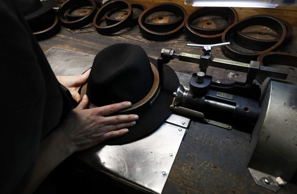 A man holds a hat inside the Borsalino hat factory, in Spinetta Marengo, near Alessandria, Italy, Thursday, Jan. 17, 2019. Borsalino's prized felt hat...