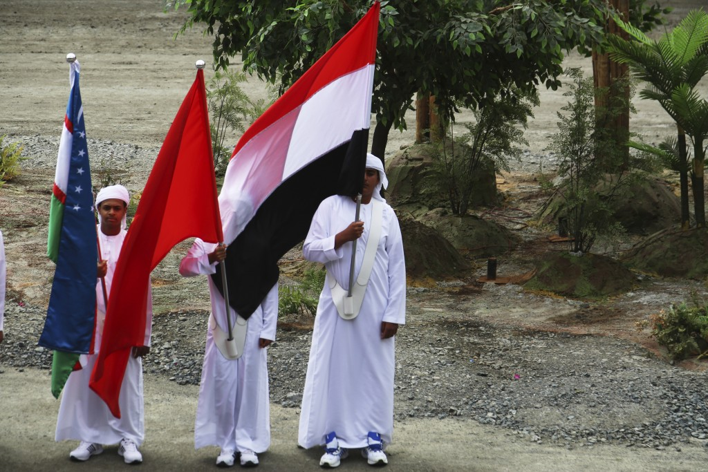 An Emirati flag-bearer gets the flag of Yemen wrapped around his face at the opening ceremony of the International Defense Exhibition and Conference i...