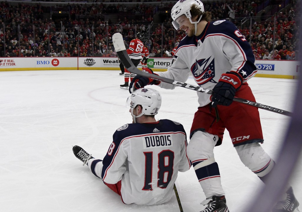 Columbus Blue Jackets center Pierre-Luc Dubois (18) gets a pat on the head from left wing Artemi Panarin (9) after he fell to the ice following a goal...