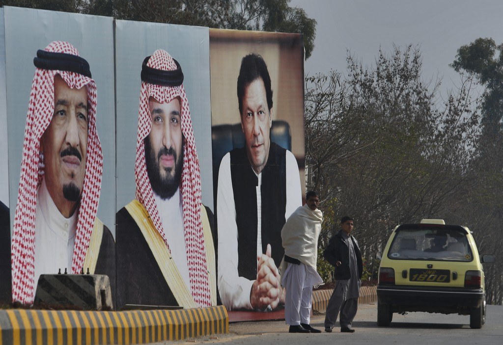 A man with his son waits for transport next to huge portraits of Saudi leaders and a Pakistani prime minister displayed on a highway on the occasion o...