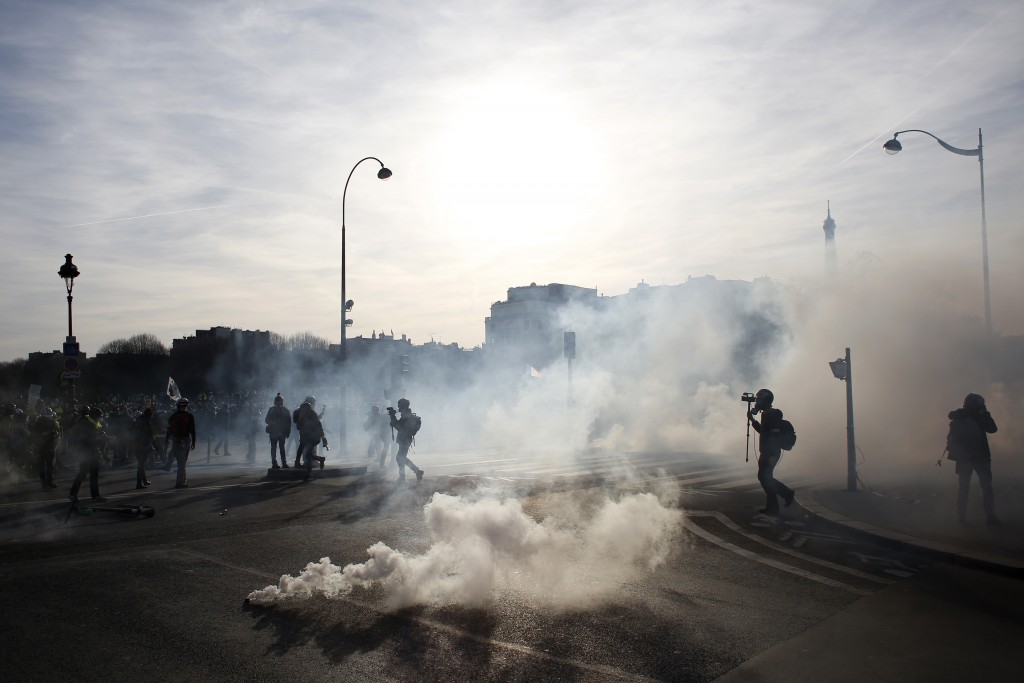 Reporters follow demonstrators during scuffles with riot police officers Saturday, Feb.16, 2019 in Paris. Hundreds of yellow vest protesters marched t...