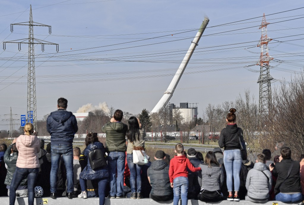People watching the fall of a chimney during the blasting of a former coal-fired power station in Dortmund, Germany, Sunday, Feb. 17, 2019. (AP Photo/...