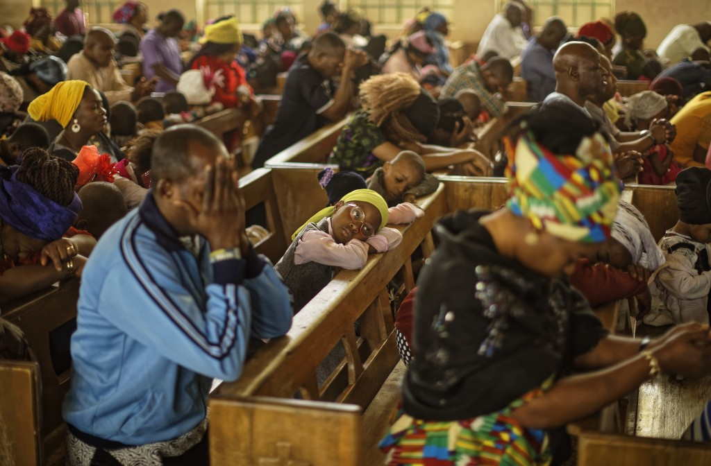 Churchgoers pray during a morning service at the Saint Charles Catholic Church, the site of a 2014 bomb attack blamed on Islamic extremist group Boko