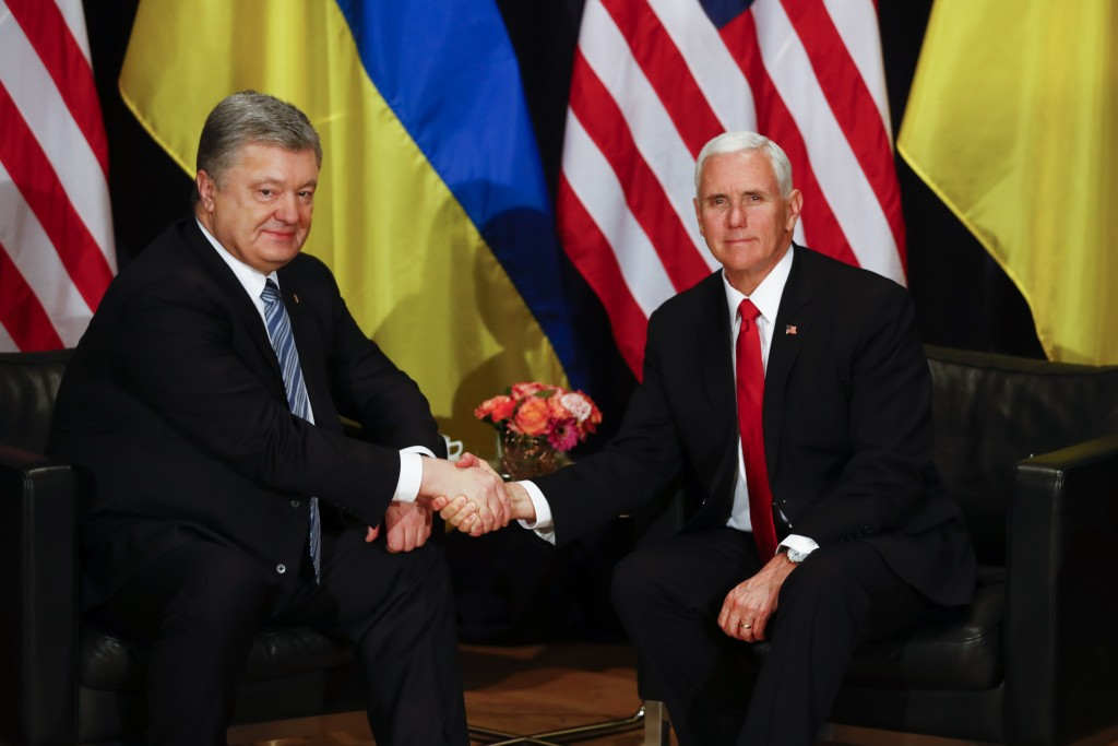 United States Vice President Mike Pence, right, and Ukrainian President Petro Poroshenko, left, shake hands during a bilateral meeting at the Munich S...