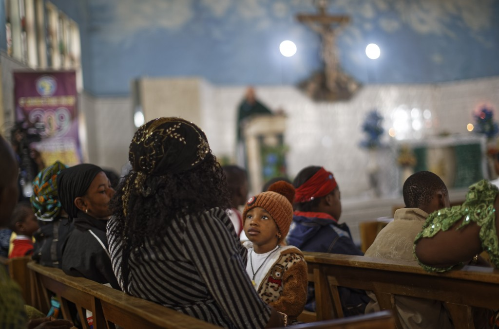 A young member of the congregation looks at her mother during a morning service at the Saint Charles Catholic Church, the site of a 2014 bomb attack b