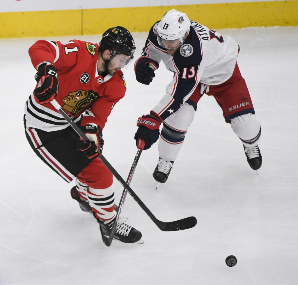 Chicago Blackhawks left wing Brendan Perlini (11) and Columbus Blue Jackets right wing Cam Atkinson (13) fight for the puck during the second period o...