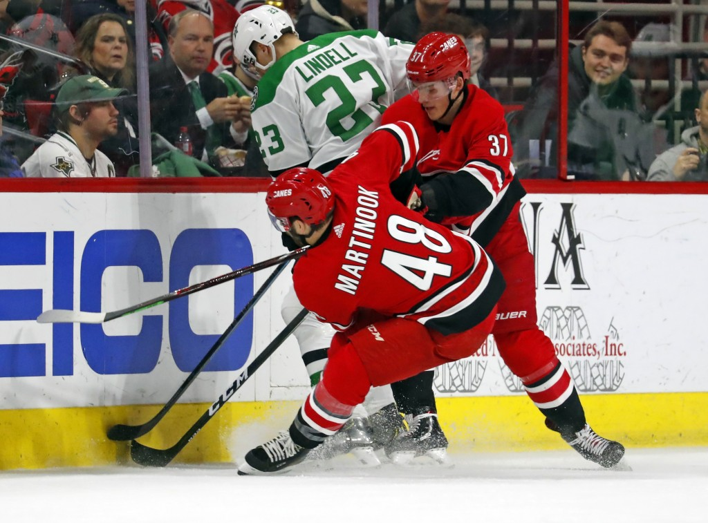 Carolina Hurricanes' Jordan Martinook (48) and Andrei Svechnikov (37) double team Dallas Stars' Esa Lindell (23) during the first period of an NHL hoc...