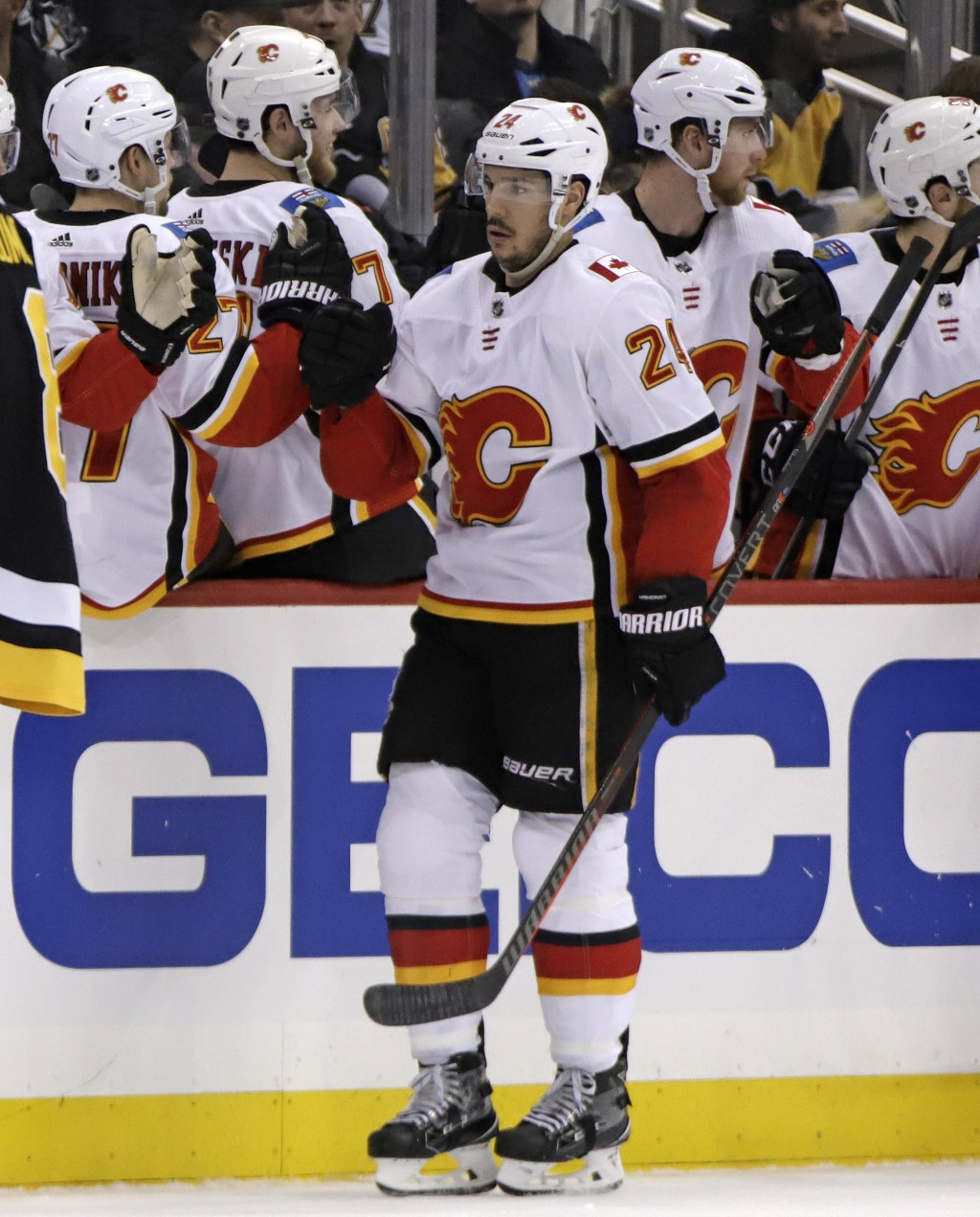 Calgary Flames' Travis Hamonic (24) celebrates his goal as he returns to the bench during the second period of an NHL hockey game against the Pittsbur...