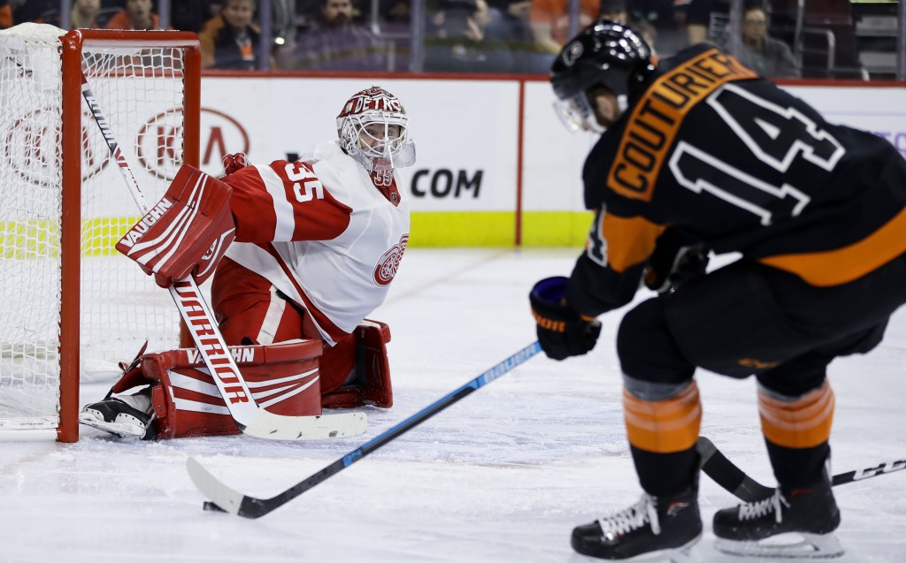 Detroit Red Wings' Jimmy Howard, left, blocks a shot by Philadelphia Flyers' Sean Couturier during the second period of an NHL hockey game, Saturday, ...