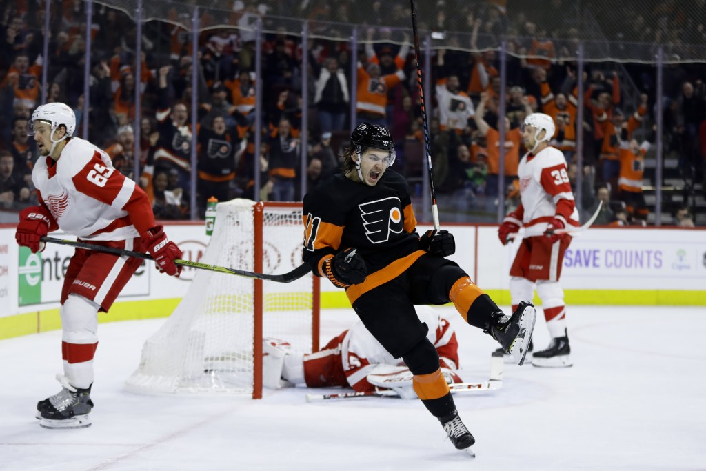 Philadelphia Flyers' Travis Konecny (11) celebrates after scoring the game-winning goal during overtime of an NHL hockey game against the Detroit Red ...
