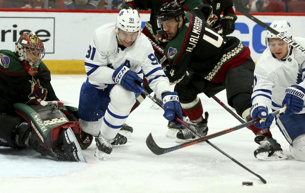 Toronto Maple Leafs center John Tavares (91) and left wing Zach Hyman (11) battle with Arizona Coyotes defenseman Niklas Hjalmarsson (4) for the puck ...