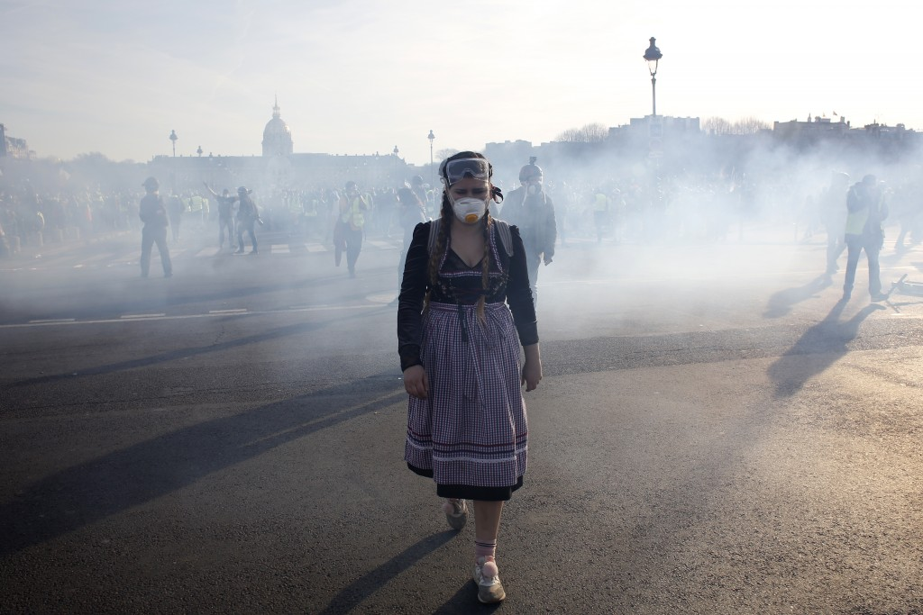 A protester walks away during scuffles Saturday, Feb.16, 2019 in Paris. Hundreds of yellow vest protesters marched through Paris, one of seven scatter...