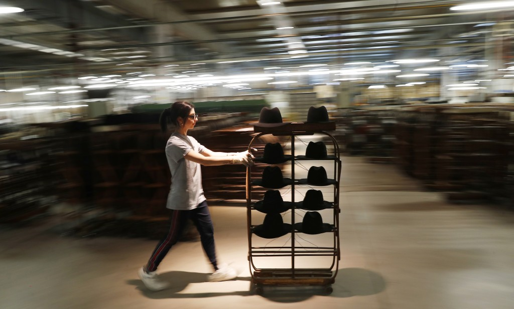 A woman worker pushes a cart with hats in Borsalino's hat factory, in Spinetta Marengo, near Alessandria, Italy, Thursday, Jan. 17, 2019. Borsalino's ...