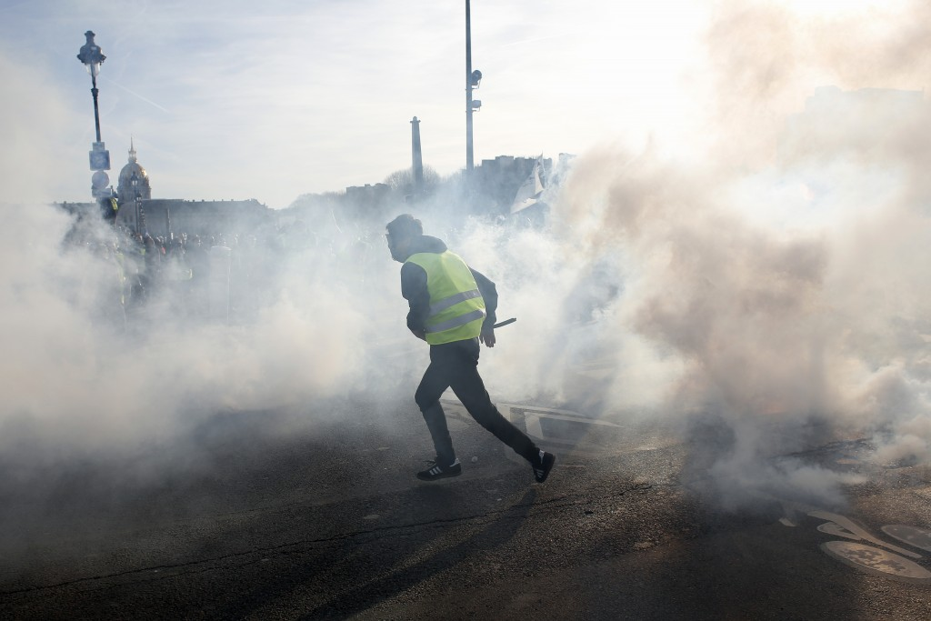 A yellow vest protester runs amid tear gas during scuffles with riot police officers Saturday, Feb.16, 2019 in Paris. Hundreds of yellow vest proteste...