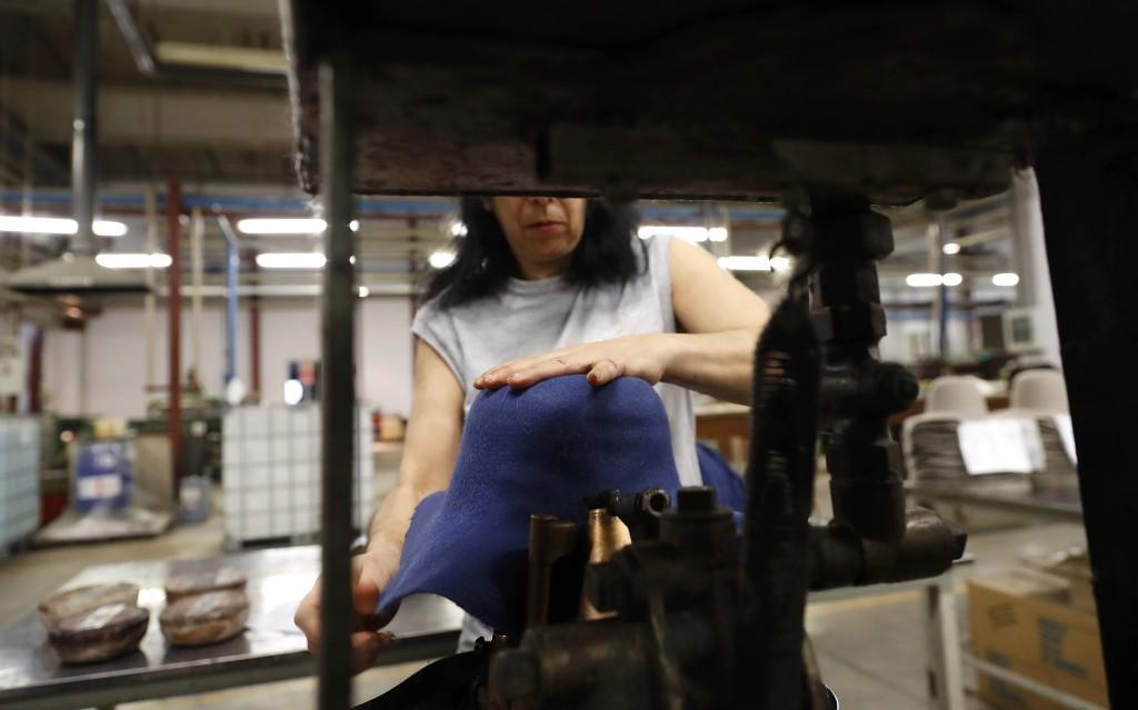 A woman moulds a hat inside Borsalino's hat factory, in Spinetta Marengo, near Alessandria, Italy, Thursday, Jan. 17, 2019. Borsalino's prized felt ha...