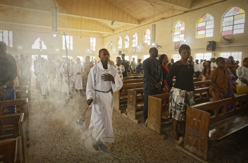 An altar boy swings the thurible of incense during a morning service at the Saint Charles Catholic Church, the site of a 2014 bomb attack blamed on Is