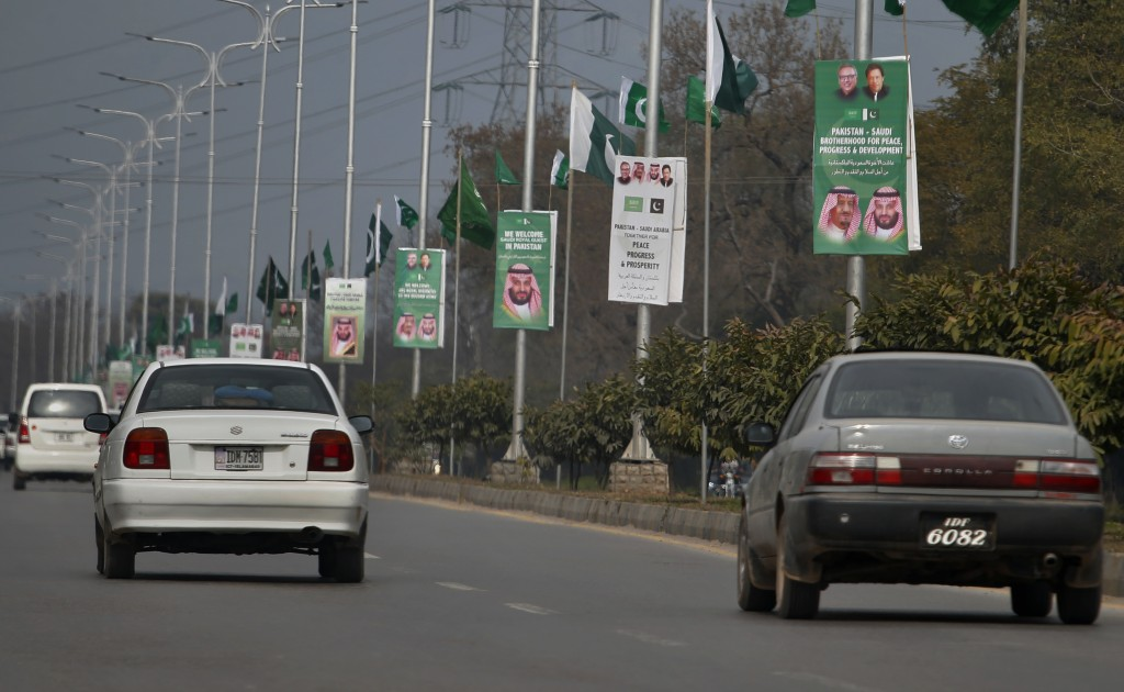 Pakistani riders drive past posters welcoming Saudi Arabia's Crown Prince Mohammed bin Salman displayed on the occasion of the visit by Saudi Arabia's...