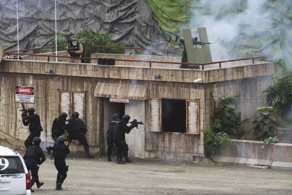 Troops raid a building during a military demonstration at the International Defense Exhibition and Conference in Abu Dhabi, United Arab Emirates, Sund...