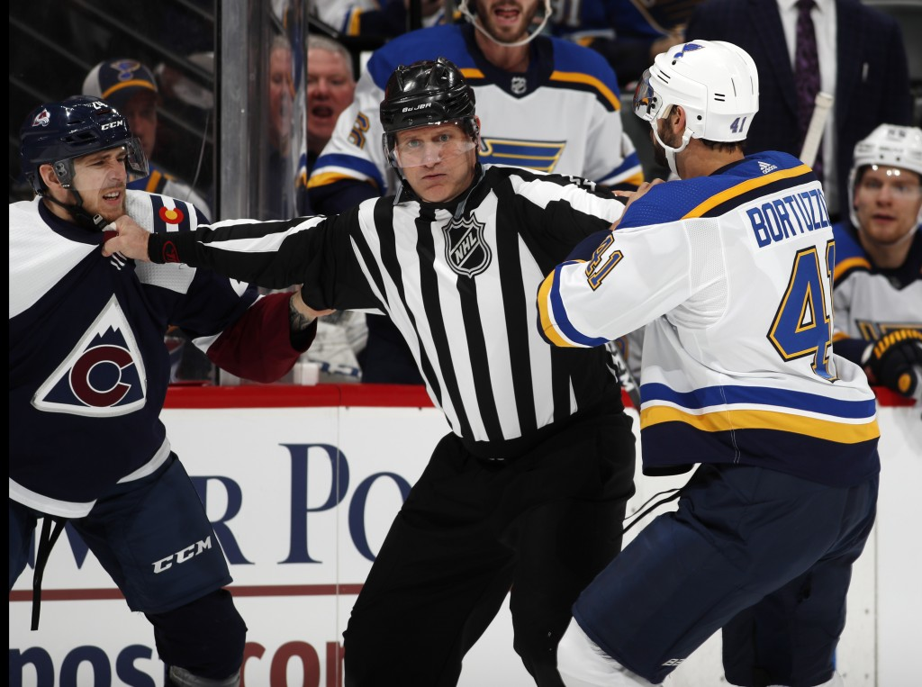 Linesman Greg Devorski, center, separates Colorado Avalanche left wing A.J. Greer, left, and St. Louis Blues defenseman Robert Bortuzzo as they try to...