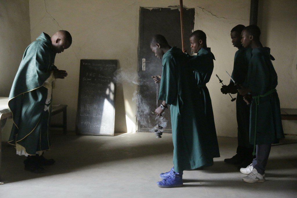 Rev. Father Maurice Kwairanga, left, prepares for a mass at St Charles Catholic Church, in Ngurore, Nigeria Sunday, Feb. 17, 2019. (AP Photo/ Sunday A...