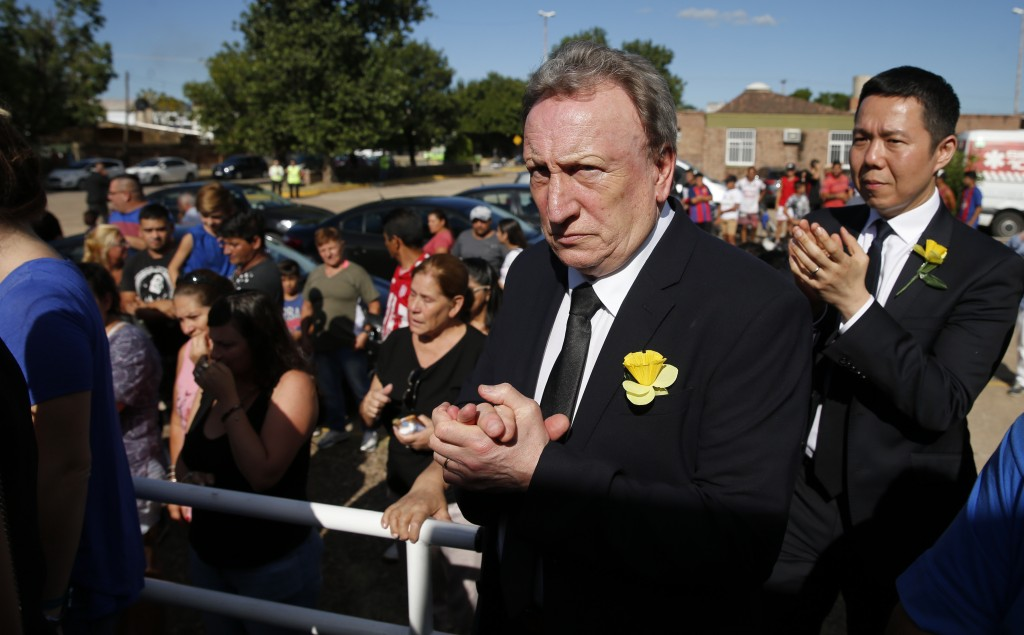 Cardiff City manager Neil Warnock, second righ, and Cardiff City CEO Ken Choo, right, applaud during the burial of Emiliana Sala, at the cemetery in S...